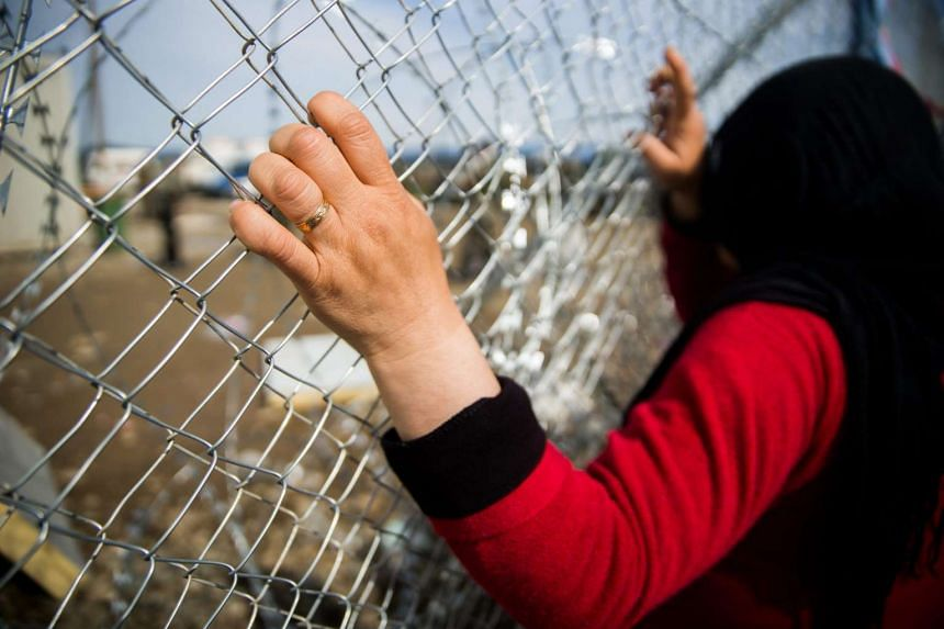 A migrant woman stands at the fence in refugee camp of Idomeni, near the Greek border with Macedonia, on March 8, 2016.