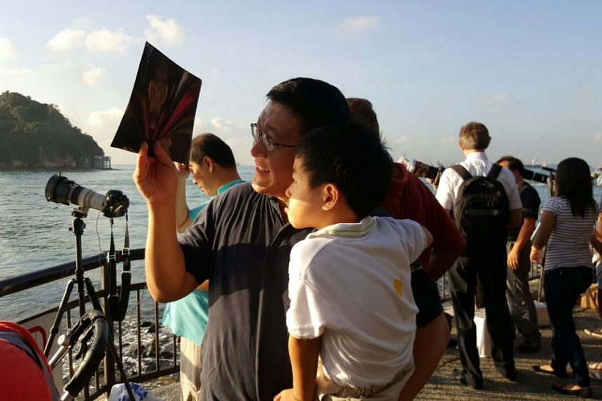 Andy Goh and his four-year-old son Patrick view the partial solar eclipse through an X-ray film.