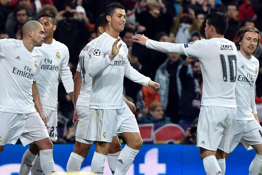 Madrid players celebrate a goal during the UEFA Champions League football match between Real Madrid FC and AS Roma at the Santiago Bernabeu stadium in Madrid on March 8, 2016.