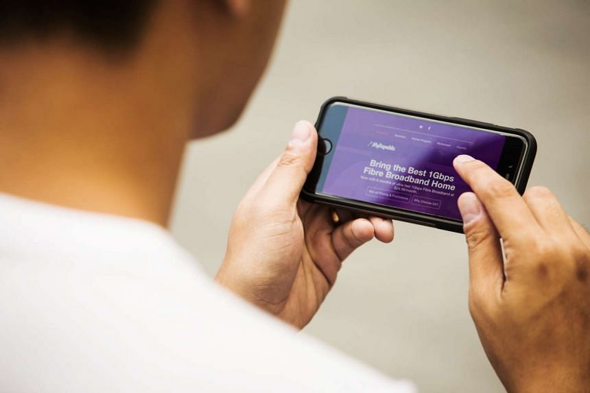 A man browsing the MyRepublic website on a smartphone in Singapore.