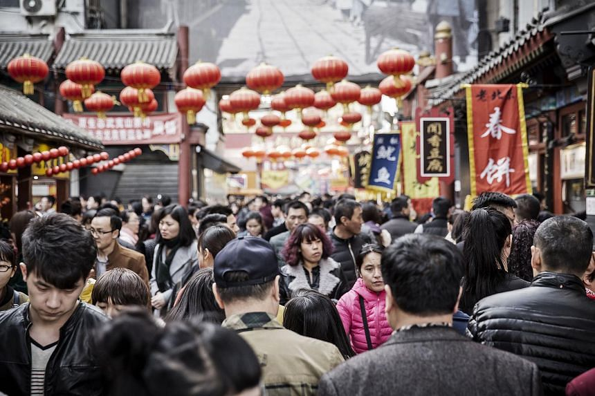 Shoppers walk past stalls at a street market in Beijing.