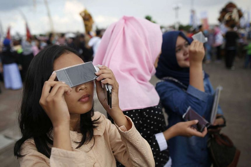 People testing filters for watching a solar eclipse near the Ampera Bridge on the Musi River in Palembang, Indonesia.