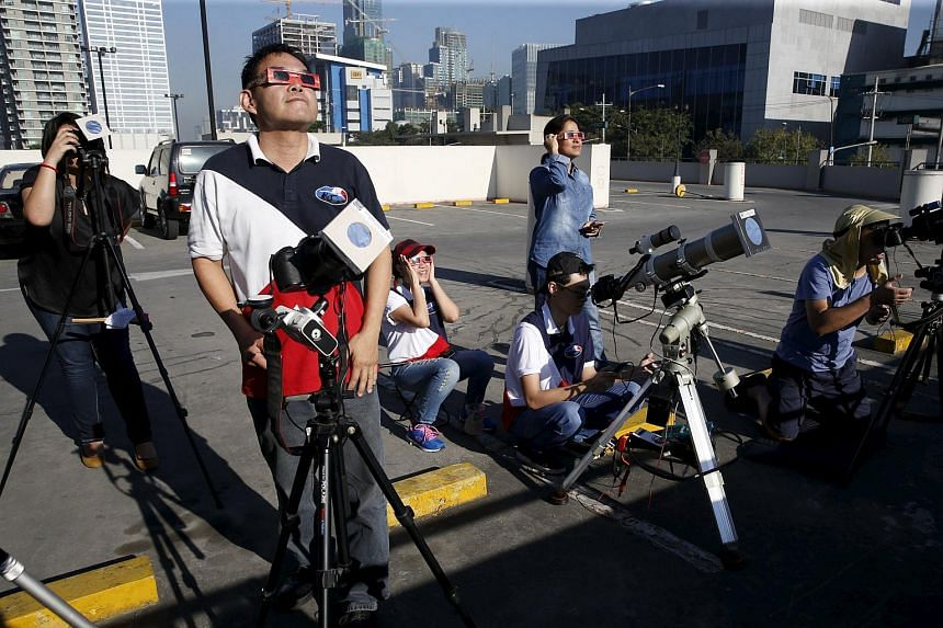 Members of Astronomical League of the Philippines taking their positions on the roof top of a parking lot as they watch the partial solar eclipse in Taguig, Metro Manila, on March 9, 2016.
