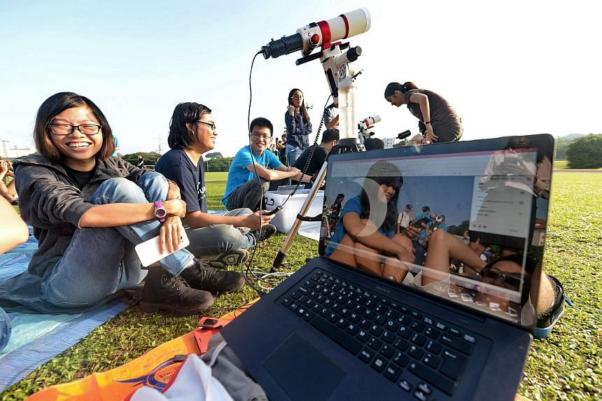 Students recording the partial solar eclipse through a telescope at a sports field at the National University of Singapore on March 9, 2016.