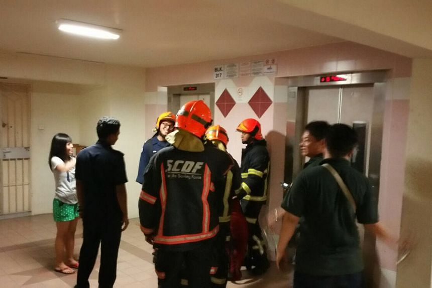 Ms Evi Lisnawati (far left), who is from Indonesia, was on her way to pick up her employer's children when she got stuck in the lift at Block 317 in Ang Mo Kio Street 31.