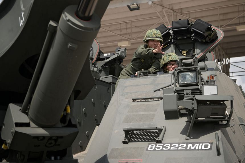 Third Warrant Officer Lee Jia Yan (far left) coaching Third Sergeant Keno Chan in an armoured engineer vehicle at Sungei Gedong Camp. When the 32-year-old 3WO Lee enlisted almost 10 years ago, there were only two other women on basic military training. In