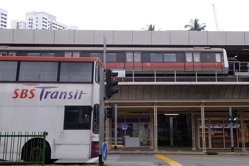 An SMRT train at a station and SBS bus at traffic junction in Ang Mo Kio.