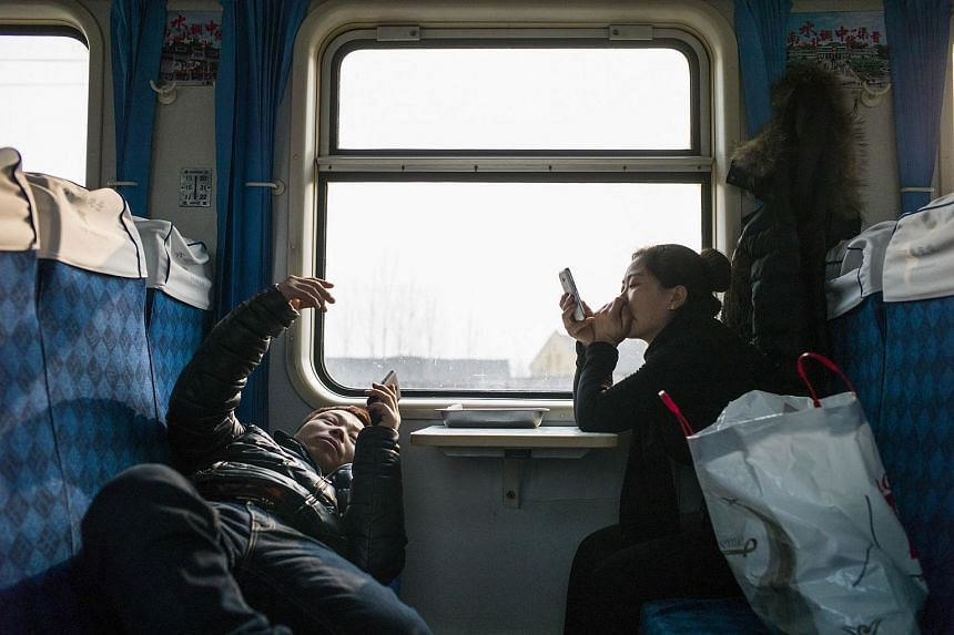 Chinese travellers waiting for the train to set off as they head to their hometown for Lunar New Year at Beijing Train Station on Jan 29, 2016.