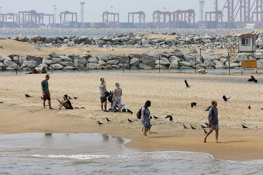 Tourists rest near the China-backed 'Port City' construction site in Colombo, Sri Lanka.