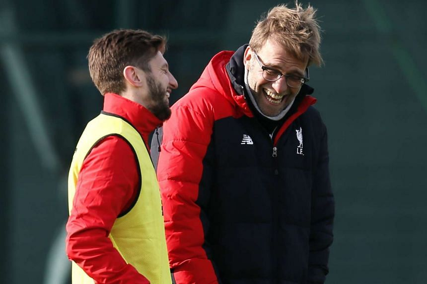 Liverpool midfielder Adam Lallana (left) speaking to manager Juergen Klopp during training.