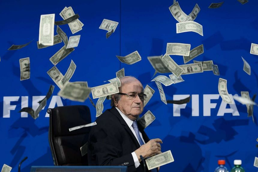This file photo taken on July 20, 2015 shows then Fifa president Sepp Blatter looking on with fake dollar notes flying around him thrown by a protester during a press conference at the football's world body headquarter's in Zurich.