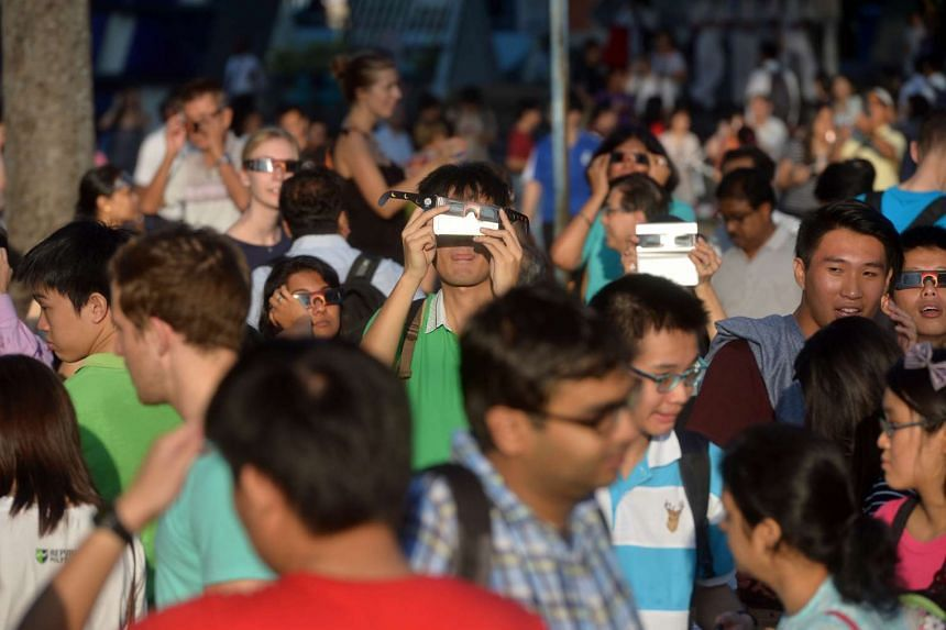 People at the Singapore Science Centre viewing the solar eclipse on March 9, 2016.