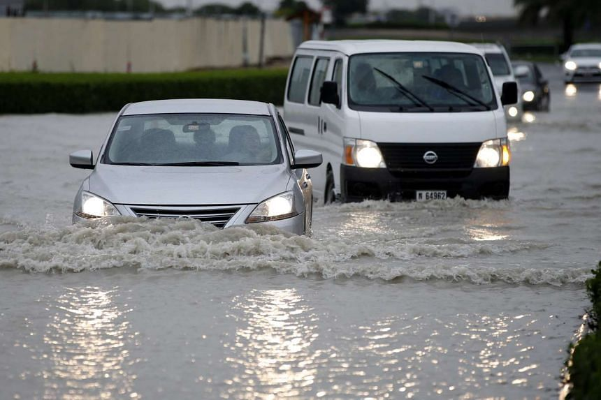 People drive their cars through a flooded street in Dubai on March 9, 2016. People drive their cars through a flooded street in Dubai on March 9, 2016.
