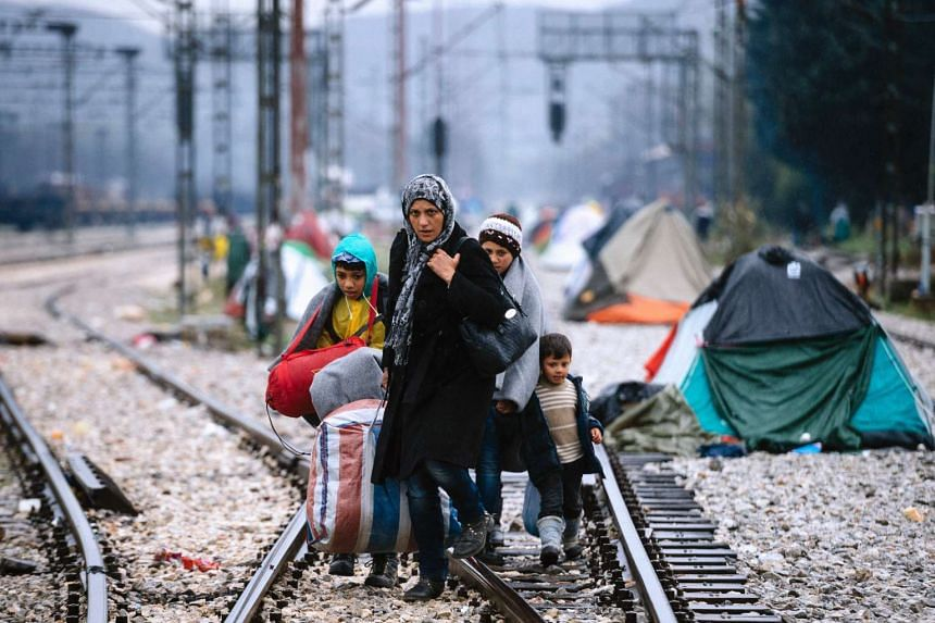 A woman and three children walk on railway tracks connecting Greece with western Europe at the Greek-Macedonian border.