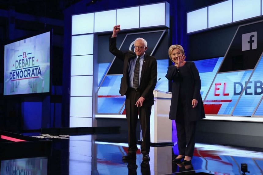 Senator Bernie Sanders (left) and Democratic presidential candidate Hillary Clinton wave to supporters before the Univision News and Washington Post Democratic Presidential Primary Debate.