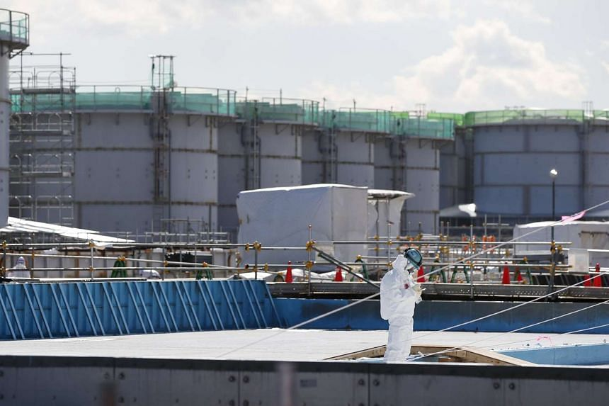 A worker taking notes in front of storage tanks for radioactive water at the Fukushima Daiichi nuclear power plant, on Feb 10, 2016.