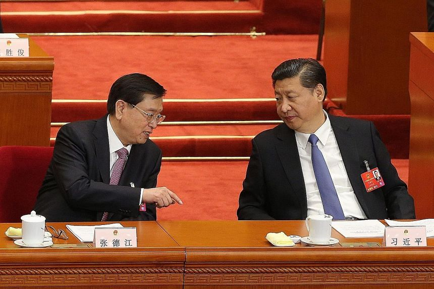 NPC chief Zhang Dejiang (left) talking to Chinese President Xi Jinping during the annual meeting of the National People's Congress at the Great Hall of the People in Beijing yesterday.