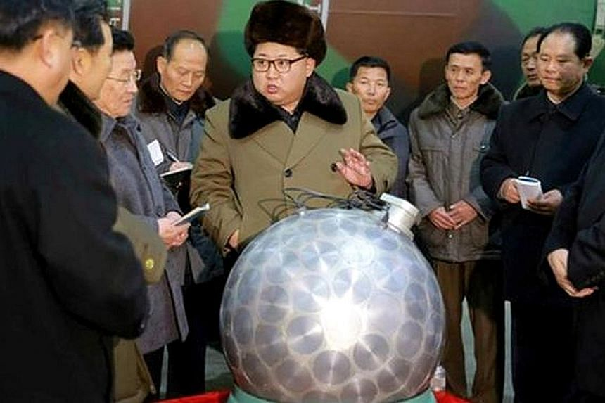 Mr Kim viewing what is supposedly a miniaturised thermonuclear warhead, in a picture released by the ruling party's newspaper.