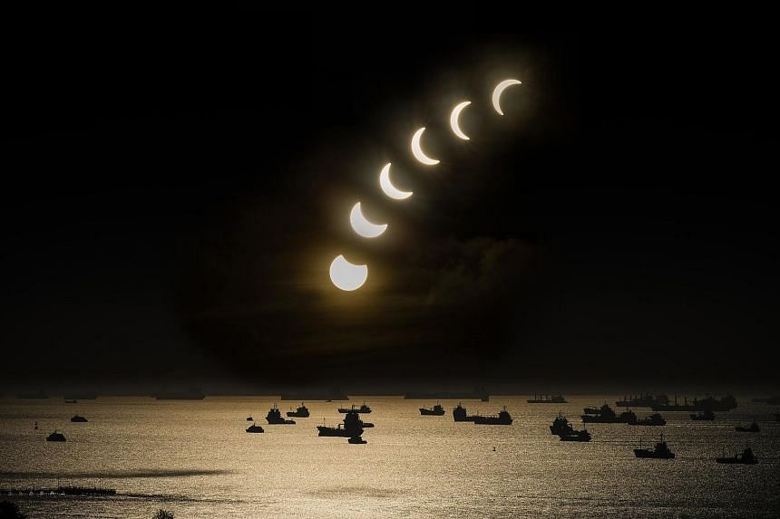 Left: In Thailand, students held up handmade shields during the eclipse in Phuket yesterday. Above: A composite image of seven photographs capturing the partial eclipse in East Coast, shot from the 20th storey of Neptune Court between 7.30am and 8.23