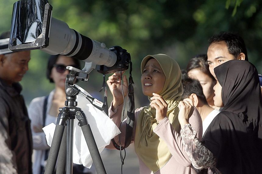 People crowding around a camera for a closer look at the solar eclipse in Jakarta yesterday, as it swept through 12 of Indonesia's 34 provinces before heading out towards the Pacific Ocean.