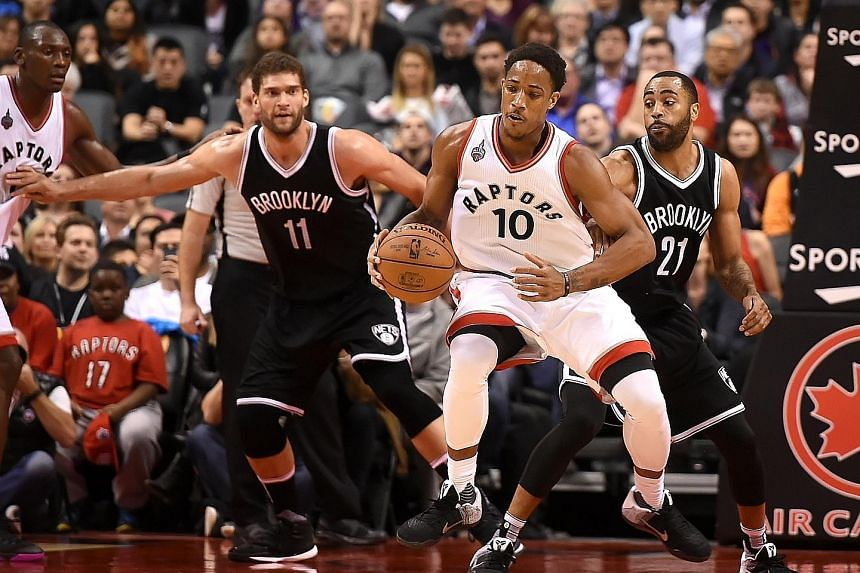Toronto Raptors guard DeMar DeRozan grabbing a loose ball in front of Brooklyn Nets centre Brook Lopez (left) and guard Wayne Ellington at Air Canada Centre. The Raptors won 104-99 after trailing by 16 points at half-time.