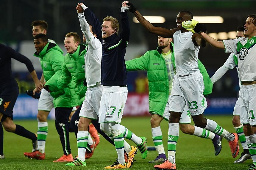 Wolfsburg forward Andre Schuerrle (in black) and his team-mates acknowledge their fans at the Volkswagen Arena after the Bundesliga side's 1-0 victory over Belgian outfit Gent sent them through to the Champions League quarter-finals for the first tim