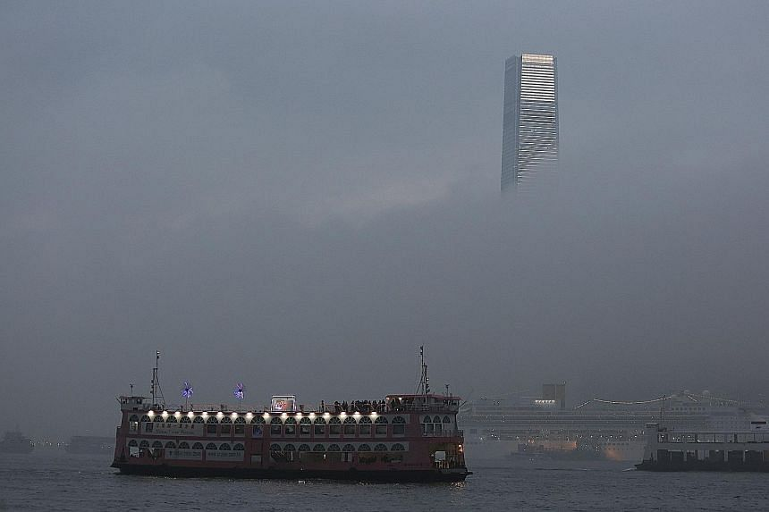 The 484m International Commerce Centre - the highest skyscraper in Hong Kong - vanishing as heavy fog cloaked Victoria Harbour yesterday. According to the Hong Kong Observatory, an intense north-east monsoon is bringing cold weather to the coastal ar