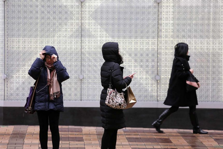 People braving the cold in Hong Kong's Tsim Sha Tsui district on Jan 24.