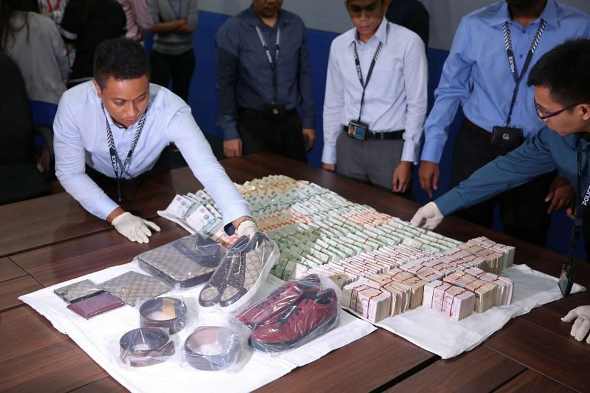 The police recovered about $433,000 in cash and several luxury goods from the Marina Bay Sands room where the men were staying.