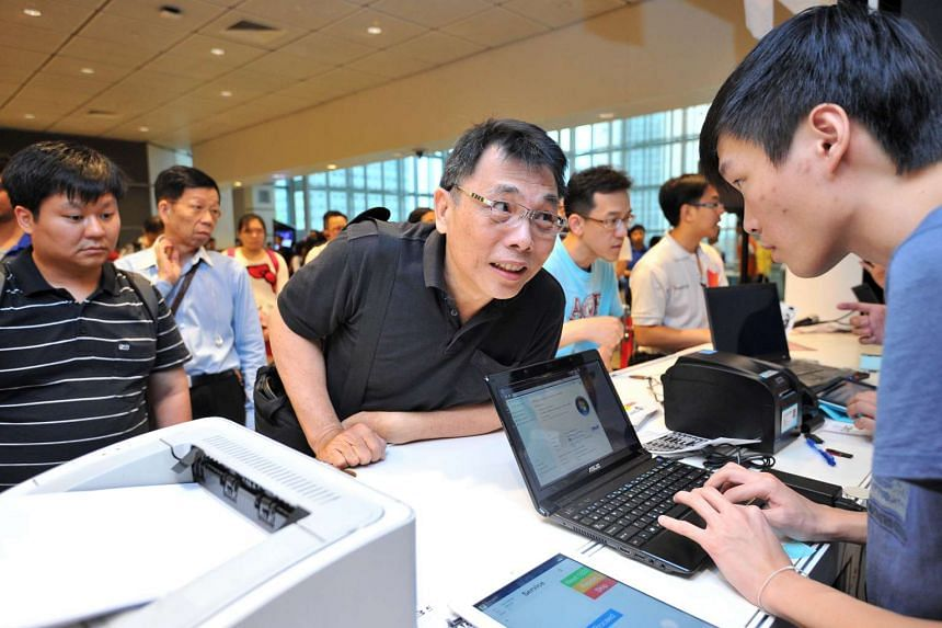 Mr Seetoh Leng (centre), a translator, trying to trade in his laptop at the Trade-In Programme at the last IT SHOW, At level 4 this year, you can trade in used laptops, tablets, smartphones and even TV sets (below 34 inches) for IT Show cash vouchers