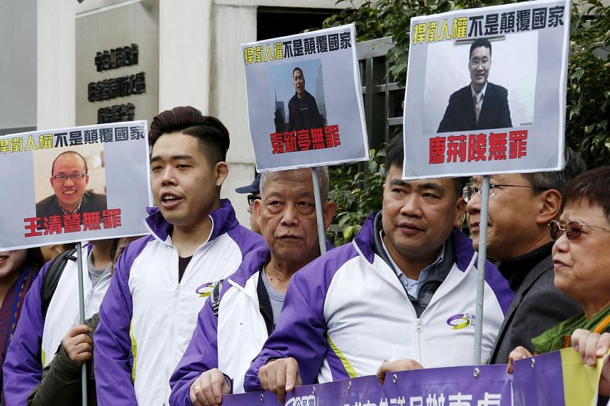 Protesters holding portraits of detained lawyers outside China's Liaison Office in Hong Kong on Jan 29, 2016.