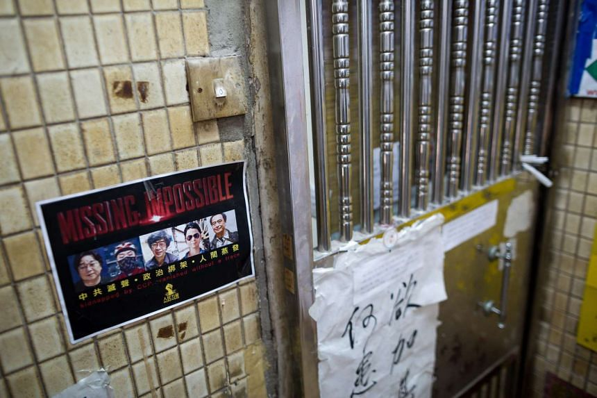 A flyer that reads 'Missing: Impossible' with the photos of 5 missing booksellers hangs on the entrance to Causeway Bay Books store in Hong Kong, China, on March 5, 2016.