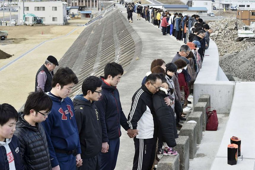 People observe a moment of silence at 2.46pm in Miyako, Iwate prefecture in Japan on March 11, 2016 to mark the fifth anniversary of the March 11 earthquake.