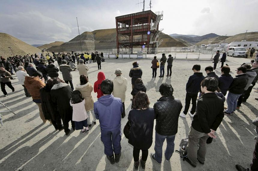 People observe a moment of silence at 2.46pm in Minamisanriku town, Miyagi prefecture, Japan on March 11, 2016 to mark the fifth anniversary of the March 11 earthquake.