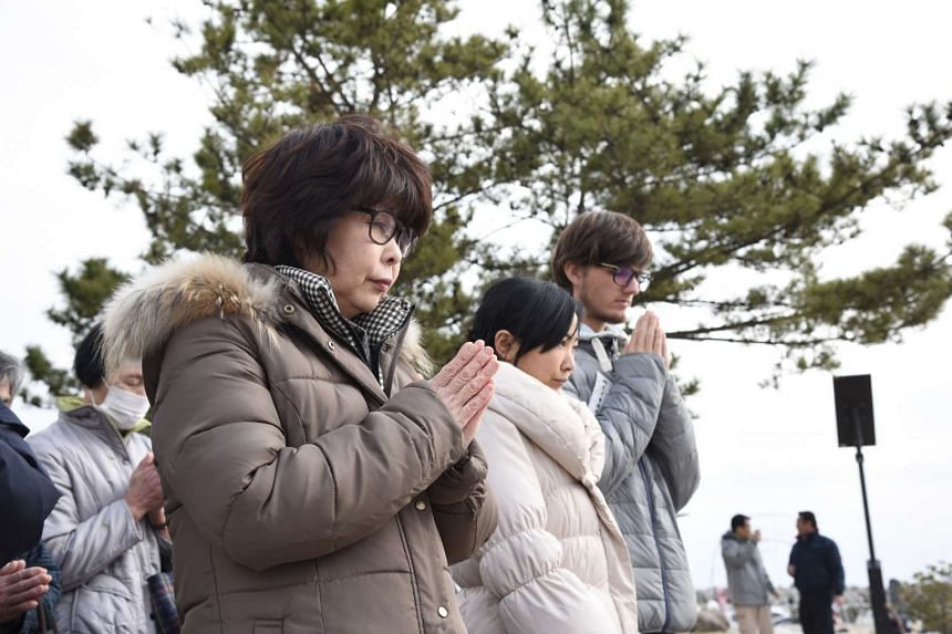 Visitors to Iwaki city put their hands together in prayer on the fifth anniversary of the March 11 earthquake.