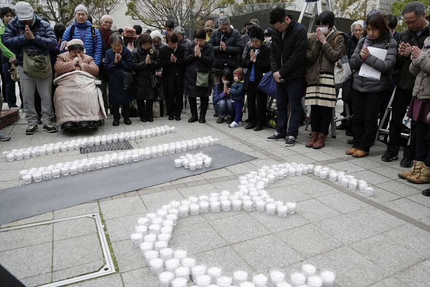 Residents in Kobe pray for the 2011 quake and tsunami victims in Kobe, Hyogo prefecture on on March 11, 2016.