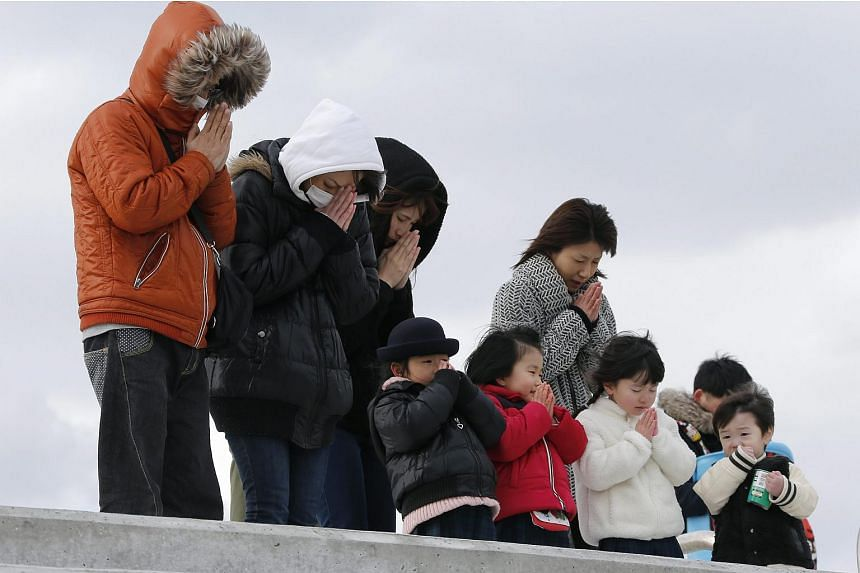 People offer a minute of silence for the victims at tsunami-devastated Abraham, coastal district of Sendai, northern Japan, on March 11, 2016.