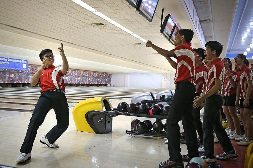 Singapore Sports School's Jarred Lim celebrates a strike with his team-mates and coach. His team clinched the bowling B Division boys' doubles and quartet events while the girls team swept the singles, doubles, quartet and all events titles to finish