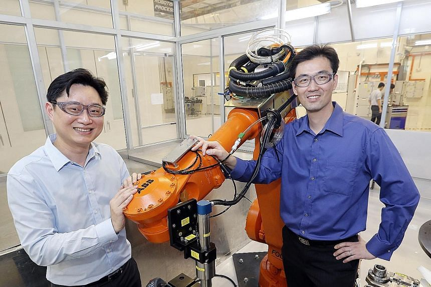 ARTC's Mr Ooi (left) and Sankei Eagle's Mr Siew with a manufacturing robot. Sankei Eagle worked with ARTC and aerospace firms to build a prototype to automate the masking process in application of coatings.
