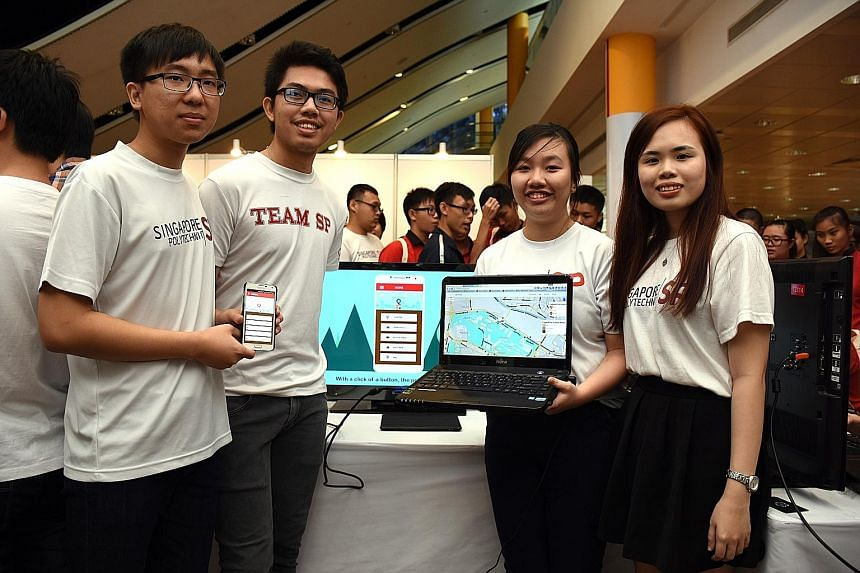 Singapore Poly students (from left) Nicolas Wee, Deswanto, Claris Tham and Lee Wei Yan demonstrating the Call Police app they designed at the school's annual Project Showcase yesterday. Fellow team member Tng Xin Kai was not pictured.