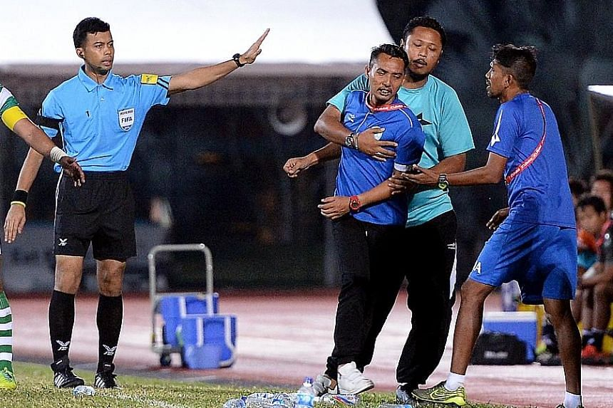 A furious Geylang coach Hasrin Jailani being restrained after his team were denied a late penalty, before he went to the stands to cool off. His hackles were increasingly raised during the game as his players missed chance after chance. At one point