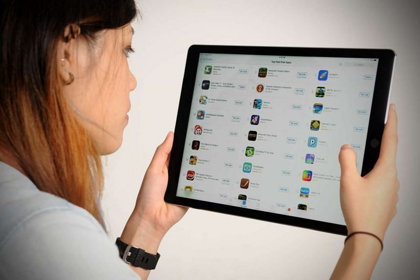 A woman looking at an app store on a mobile device.