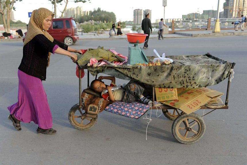 An Uighur woman pushing her fruit stall while her child lies in it along a street in Asku, Xinjiang, in 2012.