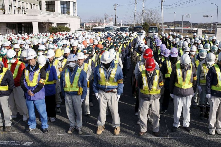 Decontamination workers observe a moment of silence to mourn victims of the 2011 earthquake and tsunami disaster, on March 11, 2016.