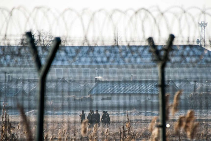 North Korean soldiers patrol next to the border fence near the town of Sinuiju across from the Chinese border town of Dandong, on Feb 10, 2016.
