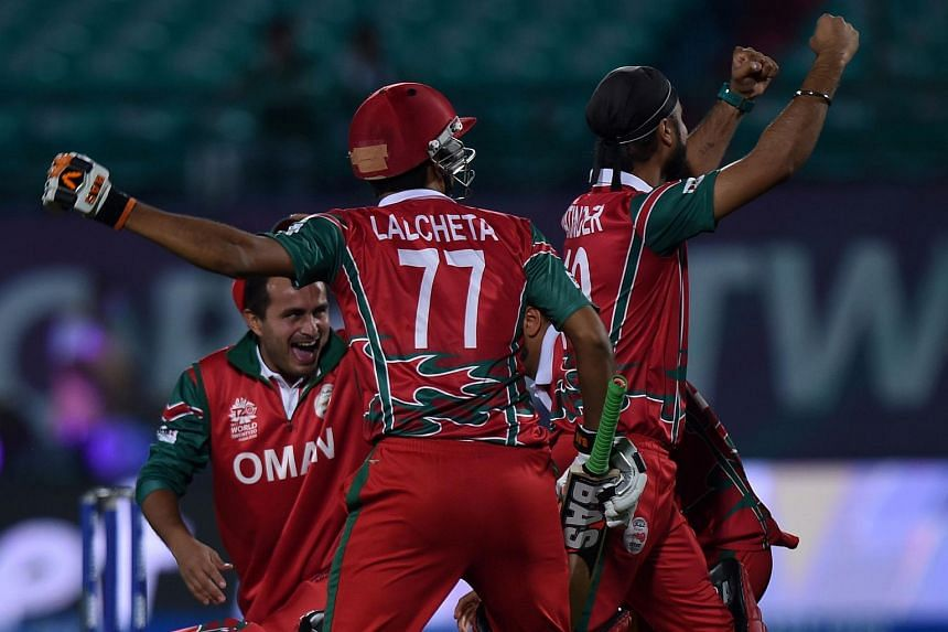 Oman's Ajay Lalcheta (centre) celebrating with his teammates after their victory in the World T20 cricket tournament against Ireland in Dharamsala on March 9.