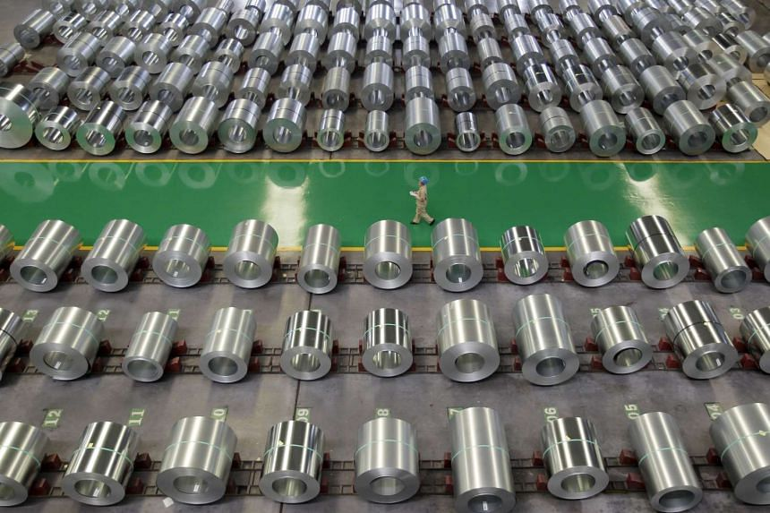 An employee walks past columns of steel at a steel production factory in Wuhan, in this August 2, 2012 file photo.