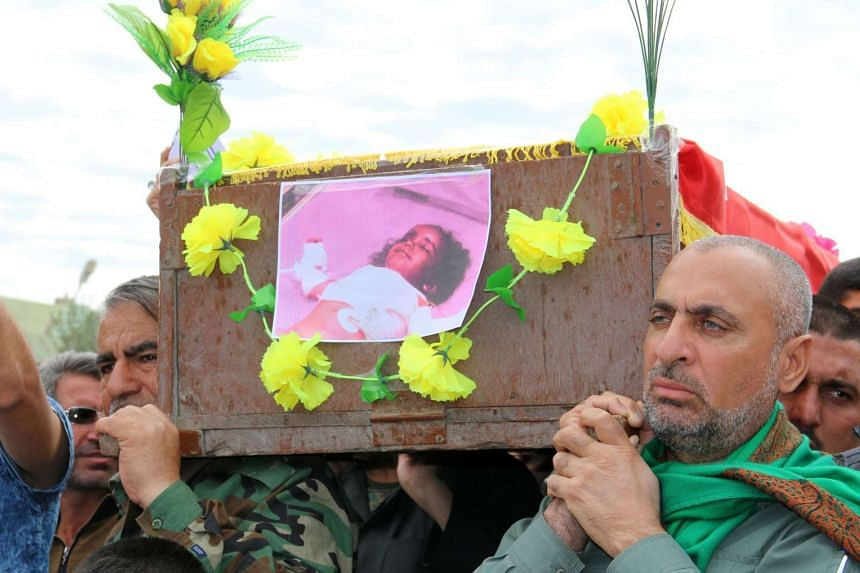 A man carrying the coffin of his three-year-old daughter, who was killed following a chemical attack.