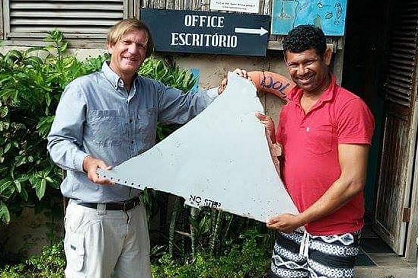Mr Gibson (right) and Mr Suleman with the plane fragment they found off the coast of Mozambique. The piece of debris is now in Malaysia for analysis.