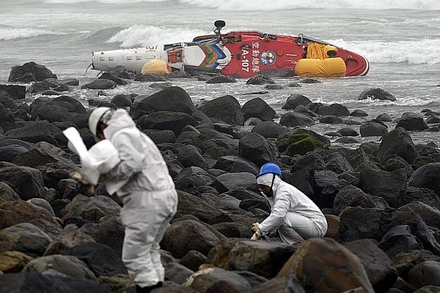 One passenger was killed when a rescue helicopter with five on board lost control and plunged into waters off New Taipei City in northern Taiwan yesterday. The helicopter had been monitoring an oil spill from a cargo vessel (in the background) that b